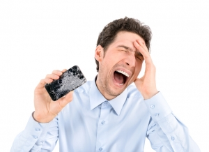 Angry man showing broken smartphone